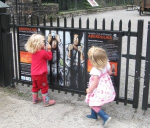 Interpretation Panel at Aberdulais Tin Works. Situated outside the gates to the site, the panel was designed to be intrigueing from a distance and thus entice visitors to look into the site and also provide a glimpse into the story and characters of the Tin Works.